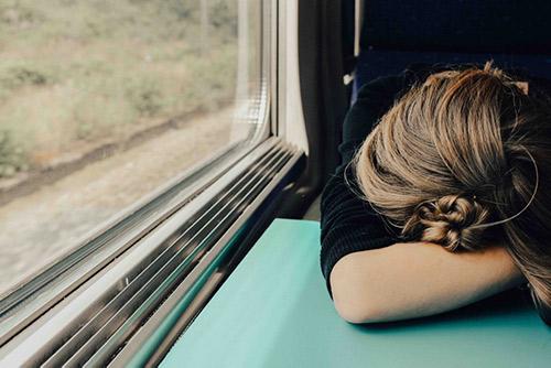 femme endormie sur une tablette dans un train